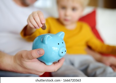 Father and child putting coin into piggy bank. Education of children in financial literacy. Money, cash, investment.