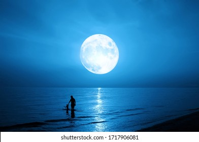Father and child silhouette. Sea and full moon