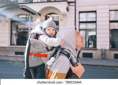 Father with child son in carrier backpack at old center of Ljubljana, Slovenia. Dad and his kid walking in city street. Travel and tradition of Europe.