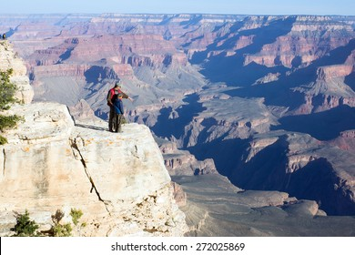 Father with child stand on a cliff. Adult explains how formed the Grand Canyon in Arizona
