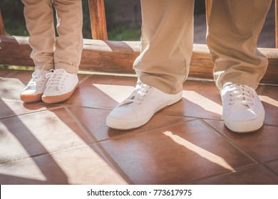Father and child standing next to each other in white sneakers closeup of feet