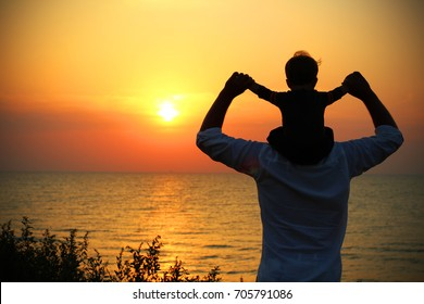 Father and child standing on the sea shore and looking into the distance in the sunset. Father and lovely baby resting in the sea in the evening.