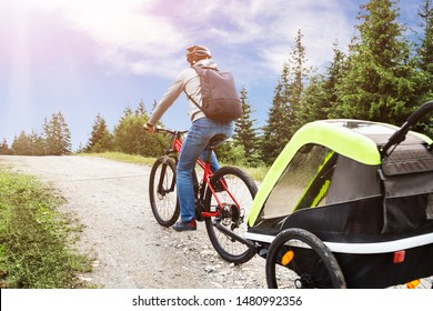 Father With Child In Trailer Riding Mountain Bike In Alps