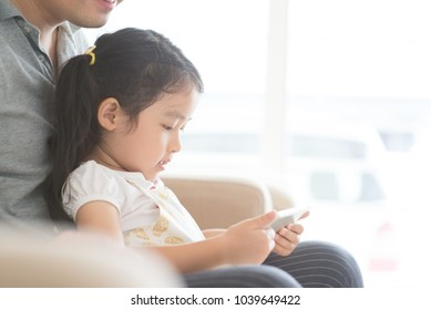 Father and child using digital tablet on sofa. Asian family at home, living lifestyle indoors.