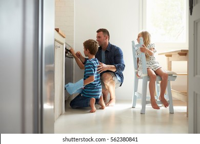 Father And Children Baking Homemade Pizza In Oven