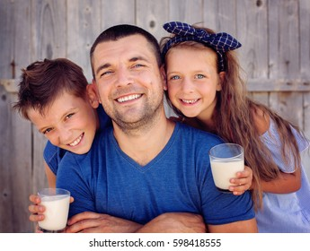 Father with children are drinking milk and having fun.