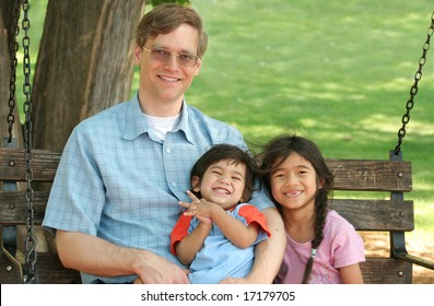 Father and children enjoying swinging in the park