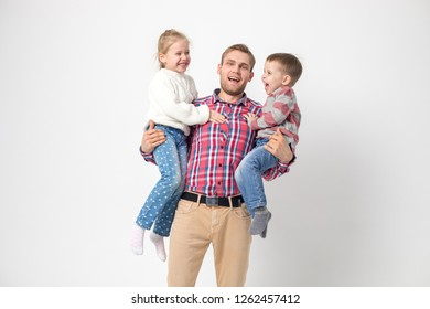 Father with children having fun on a white background. Father holds daughter and son.