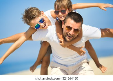 Father with children having fun on the beach at the day time.