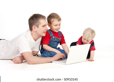 Father and children lying on the floor with laptop