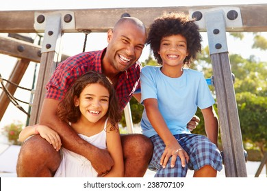Father With Children On Playground Climbing Frame