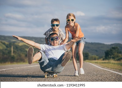Father and children playing on the road at the day time. People having fun outdoors. Concept of friendly family.