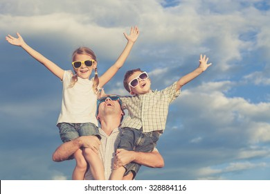 Father and children playing in the park  at the day time. Concept of friendly family. Picture made on the background of blue sky.