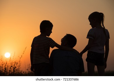 Father and children playing in the park at the sunset time. People having fun on the field. Concept of friendly family and of summer vacation.