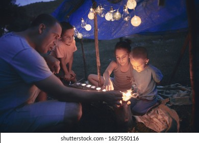 Father with children playing under their backyard tent with lanterns.