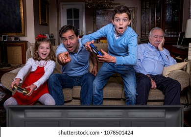 Father and children playing with a video game and grandfather sleeping