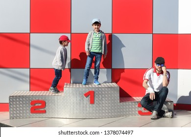 father and children in a podium the first happy, the second bad looser and the third indifferent