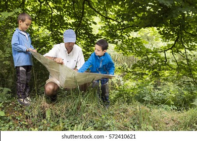 Father and children reading map in a wild green forest nature.