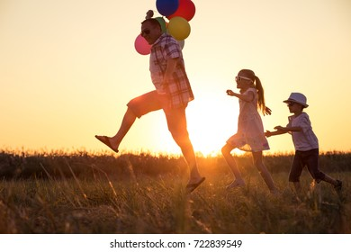 Father and children running on the road at the day time. Concept of happy family.