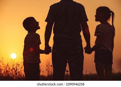 Father and children standing in the park at the sunset time. People having fun on the field. Concept of friendly family and of summer vacation.