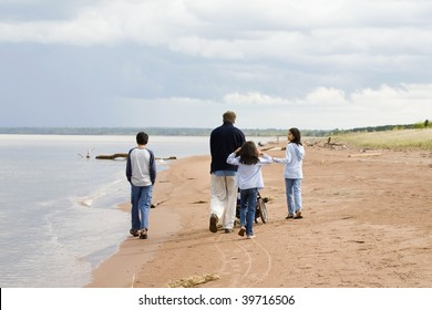 Father and children strolling along the deserted lake shore on sunny day