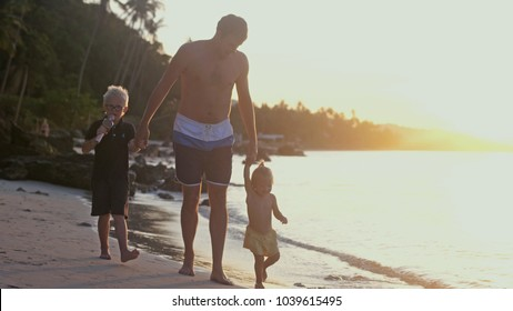Father with children walking on the beach at beautiful sunset. Travel holiday concept