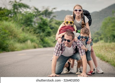 Father and children walking on the road at the day time.  Concept of friendly family.