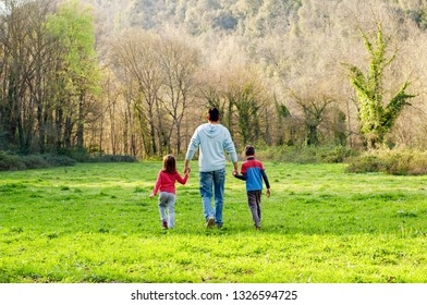 Father with children walking out of town through the countryside. Family rural travel.