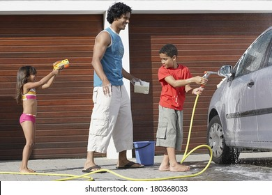 Father and children washing car at home
