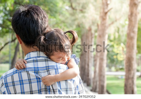 Father and child,sad little girl resting on her father's shoulder in the park