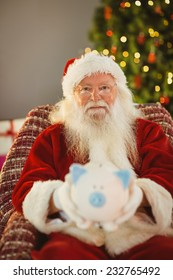 Father christmas offering piggy bank at home in the living room