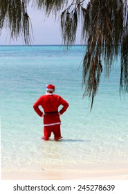 Father Christmas on Boxing Day, relaxing on a tropical island in the ocean still in his Father Christmas suit, celebrating the end of a long night