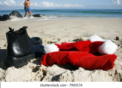 Father Christmas on Boxing Day at the beach, after the busiest night of the year, showing his hat, clothes and him walking  on the beach in his swimmers and the ocean in the background