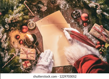 Father Christmas writing a seasonal letter using a vintage feather quill pen on old yellowed paper surrounded by Xmas decorations, gifts and snow