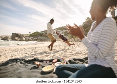 Father circling his son on the beach with mother clapping hands. Happy family enjoying themselves on the beach.