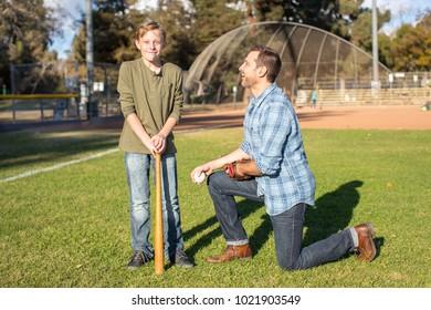 Father coach teaching son baseball