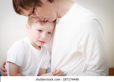 father comforting her crying little son - parenthood concept