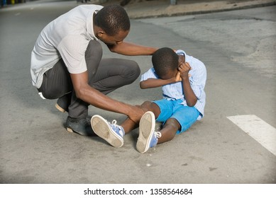 Father comforting his son crying, child fallen on the road having a knee injury