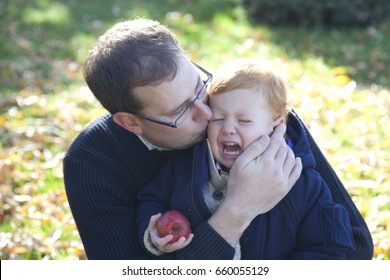 father comforts crying son child