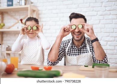 Father is coocking with daughter. Father's Day concept. A little girl and dad have fun in the kitchen. Cucumber instead of eyes.