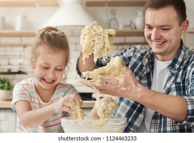 Father is cooking pastry with daughter first time in kitchen. Happy man and little girl kneading too liquid dough and laughing, fail with recipe, copy space