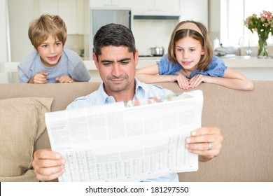 Father and cute children reading newspaper at home