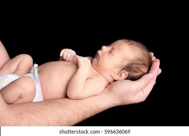 Father with cute sleeping baby on black background