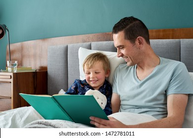 Father dad in bed with son reading stories story telling at bedtime, closeness relationship love bonding