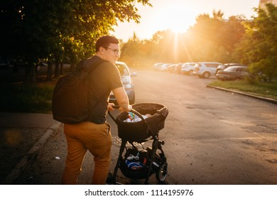 Father dad with newborn pram stroller outside suring summer evening sunset in the city streets; family leisure bonding concept