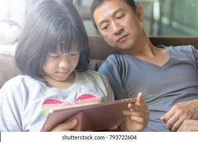 Father and daughter activity technology together concept. Asia kid girl reading e-book or playing game on computer tablet while dad watching as parental guidance for PG13.
