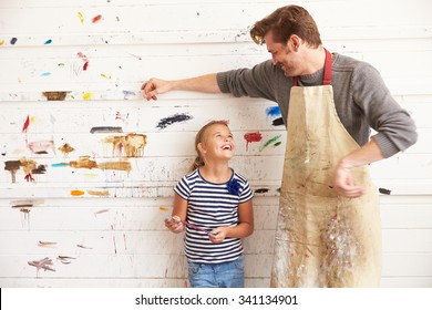 Father And Daughter Against Paint Covered Wall In Art Studio