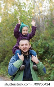 Father and daughter in an autumn forest. The girl is sitting on man's shoulders with her hands up. They are looking happy. Shot with soft focus.