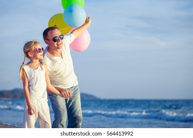 Father and daughter with balloons playing on the beach at the day time. People having fun outdoors. Concept of friendly family.