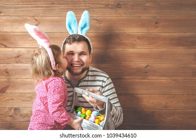 Father and daughter in bunny ears with colorful eggs in busket. Easter day. Modern Family preparing for Easter. Kids painting eggs on wooden background. Having fun on Easter egg hunt.
